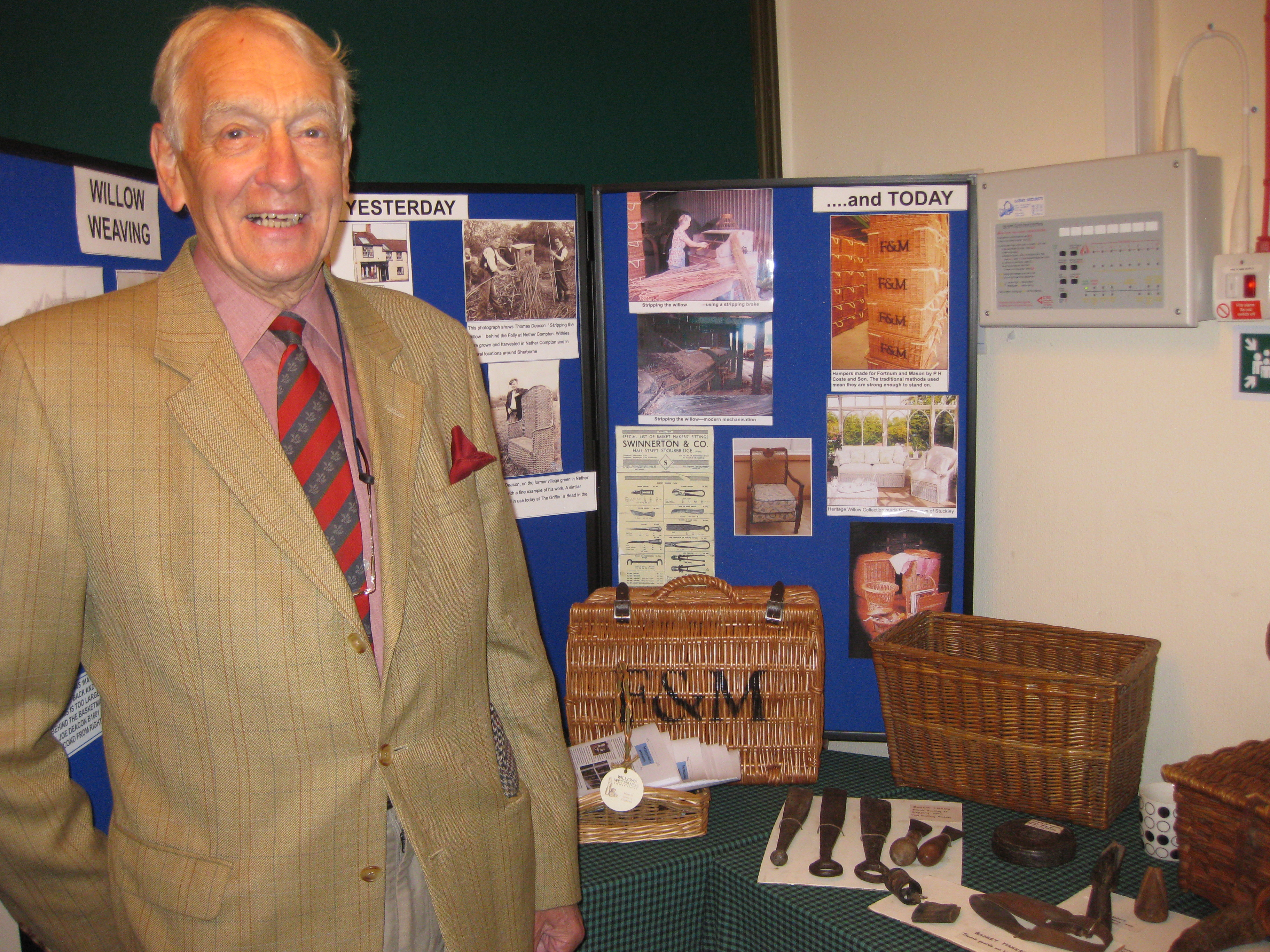 Col Iain Swinnerton standing beside the old basketmaking tools made by his family firm.